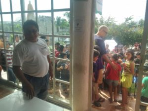 Gilly watches as the crowd of children anxiously await him to open the door. Thank you Gilly!